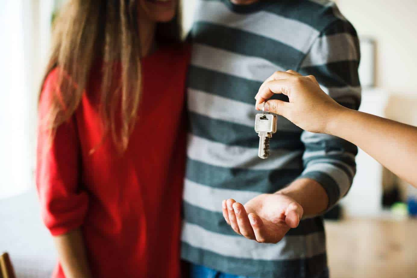person handing over house keys
