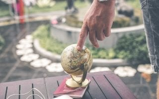 Man's finger touching globe
