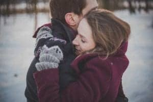 man and woman hugging in the snow