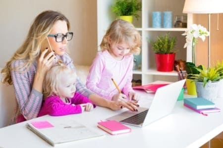 mom working on laptop with two kids