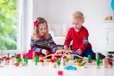 boy and girl building train track