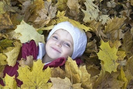 Girl lying in yellow leaves