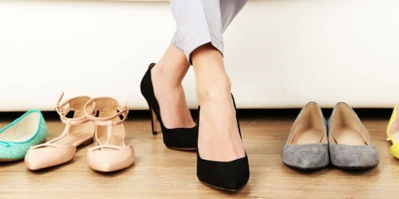pair of ladies feet in black shoes surrounded by more shoes