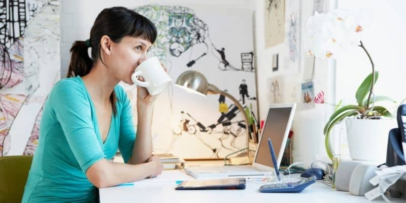 woman drinking coffee while working on laptop as a virtual assistant