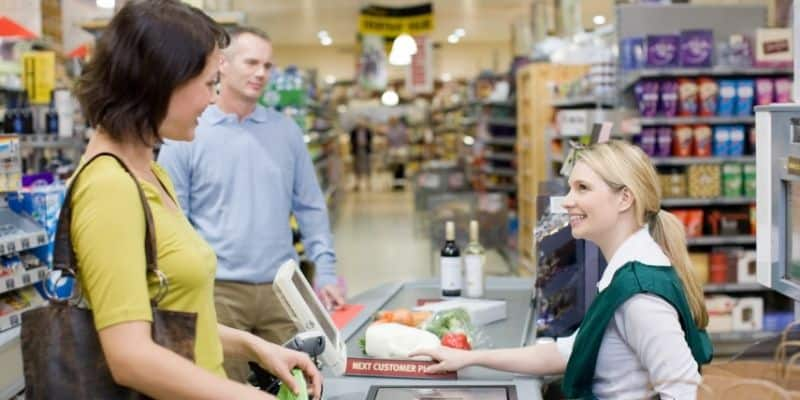 woman at supermarket checkout with checkout assistant smiling at her, man behind waiting with groceries