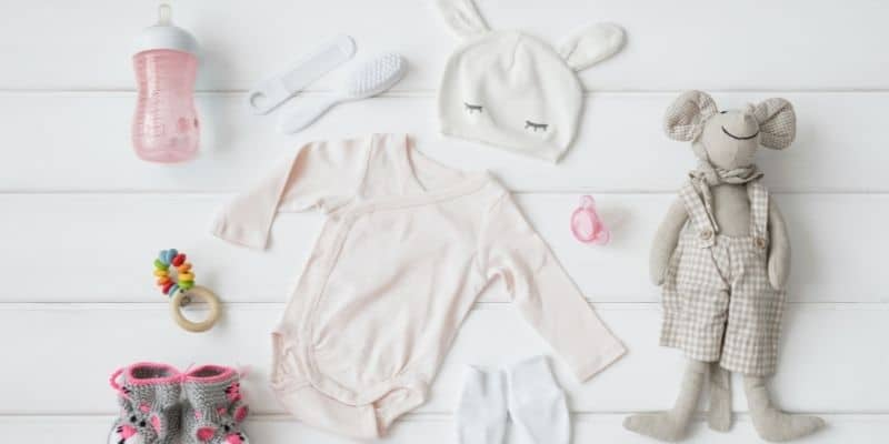 flat lay of baby items on white background, including babygro, hat, brush and comb, pink bottle, pacifier, grey teddy and booties.